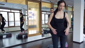 Two women in black sportswear doing aerobics with special benches in gym. stock footage