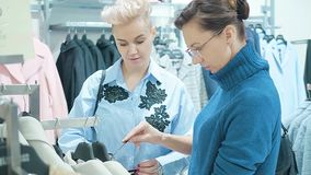 Two women at a boutique choosing a dress. Two women at a boutique choosing a dress stock footage