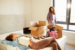 Two Women With Boxes In Bedroom Moving Into New Home. Chatting To Each Other stock photo