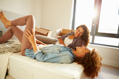 Two Women With Boxes In Bedroom Moving Into New Home. Chatting To Each Other stock photos