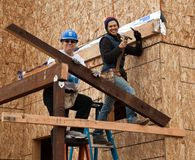 Two women build home wall for Habitat For Humanity Stock Photos