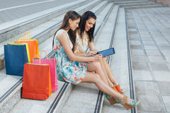 Two women buying online through a digital tablet Royalty Free Stock Images