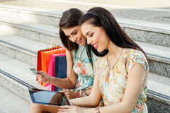 Two women buying online through a digital tablet Stock Photos