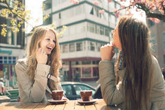 Two women in a cafe. Two young women talk and drink coffee in cafe, outdoors Royalty Free Stock Images