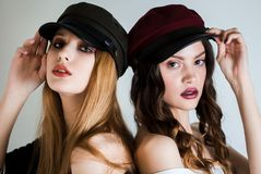 Two women in caps and with bright makeup on white background back to back looking at the camera. Fashion, cosmetics, facial care royalty free stock image
