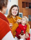 Two women caring for  toddler. Two women caring for sick toddler Royalty Free Stock Photos