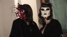 Two women in carnival costumes and masks. People dancing in a nightclub at a party. Men and women having fun, drink alcohol, get acquainted. The crowd of girls stock video footage