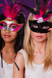 Two women with carnival venetian masks. Holidays, people and celebration concept. two women mixed race and caucasian with carnival venetian masks over festive Royalty Free Stock Photo