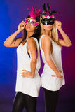 Two women with carnival venetian masks. Holidays, people and celebration concept. two women mixed race and caucasian with carnival venetian masks over over Stock Photos