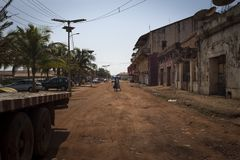 Two women carrying large bags on their heads and crossing a dirt street near the port of Bissau. Bissau, Republic of Guinea-Bissau - January 30, 2018: Two women royalty free stock image