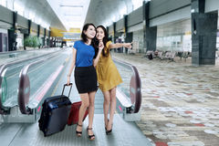 Two women carrying luggage in airport Stock Photo