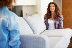 Two Women Carrying Sofa As They Move Into New Home. Horizontal Image Of Two Women Carrying Sofa As They Move Into New Home royalty free stock photos