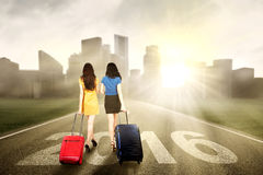 Two women carrying suitcase and walk on the road Stock Photo