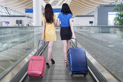 Two women carrying suitcases for traveling. Back view of two women walking on the airport escalator while carrying suitcases for traveling Stock Photo