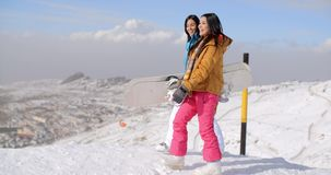 Two women carrying their snowboards on a mountain. Top at a ski resort with a panoramic view of the valleys beyond stock video footage