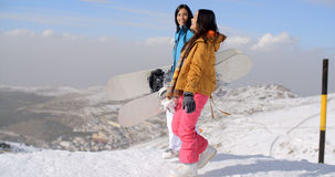 Two women carrying their snowboards on a mountain Stock Photo