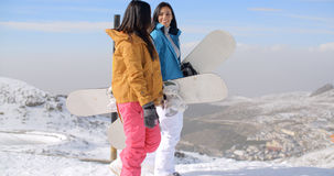 Two women carrying their snowboards on a mountain Royalty Free Stock Photography