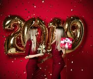 Two women celebrating at new year party happy laughing girls in casual dresses throw gold stars confetti with 2019 balloons stock photos
