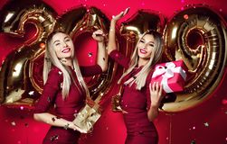 Two women celebrating at new year party happy laughing girls in casual dresses throw gold stars confetti with 2019 balloons royalty free stock photo