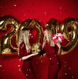 Two women celebrating at new year party happy laughing girls in casual dresses throw gold stars confetti with 2019 balloons royalty free stock photos