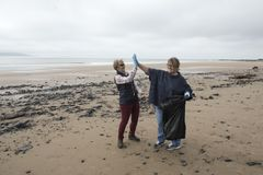 Two women celebrating after picking up rubbish. On the beach Royalty Free Stock Image