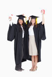 Two women celebrating their graduation. Against a white background Stock Photography