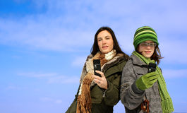 Two women with cellphones. A view of two women outdoors, wearing winter clothing and holding cellphones.  Isolated against sky background Royalty Free Stock Photography