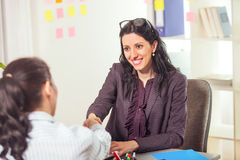 Two women chat to each other in the office. Stock Photo