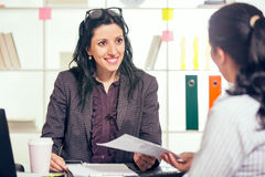 Two women chat to each other in the office. Royalty Free Stock Image
