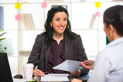 Two women chat to each other in the office. Royalty Free Stock Images