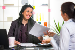 Two women chat to each other in the office. Stock Image