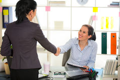 Two women chat to each other in the office. Stock Images