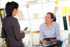 Two women chat to each other in the office. Stock Photography