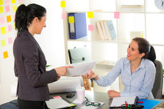 Two women chat to each other in the office. Royalty Free Stock Photos