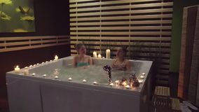 Two women chatting in a bath about spa treatments that they can get in spa salon. Two women are talking in the whirlpool with water bubbles about the spa stock footage