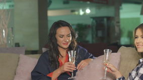 Two women chatting, drinking champagne and smiling in home. In full HD stock video footage