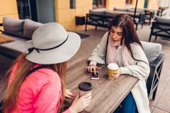 Two women chatting while having coffe in outdoor cafe. Happy friends using phone checking pictures. Girls hang out. And having fun royalty free stock image