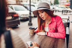 Two women chatting while having coffe in outdoor cafe. Happy friends using phone checking pictures. Girls hang out stock photography