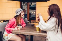 Two women chatting while having coffe in outdoor cafe. Happy friends using phone checking pictures. Girls hang out royalty free stock photo