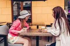 Two women chatting while having coffe in outdoor cafe. Happy friends using phone checking pictures. Girls hang out royalty free stock photography