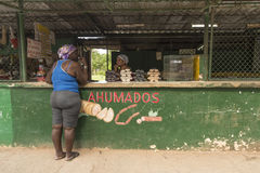 Two women chatting over streetside store counter Havana royalty free stock image