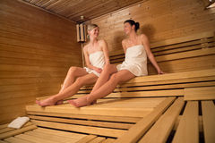 Two women chatting while relaxing at sauna Stock Images