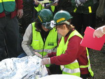 Two women checking injured men on stretcher. Two women from community respond team  are wearing bright yellow safety vest,  green construction helmet with Stock Photos