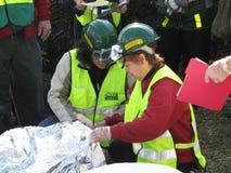 Two women checking injured men on stretcher Stock Photos