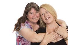 Two Close Friends Posing. Two women cheek to cheek for a photograph, on white background royalty free stock photo