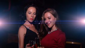 Two women cheers and clink glasses with champagne. And have fun on party stock video footage