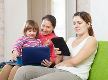 Two women and child  looks  devices. Two women and child  looks electronic devices in home interior Stock Images