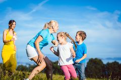 Two women with children playing tag royalty free stock photos