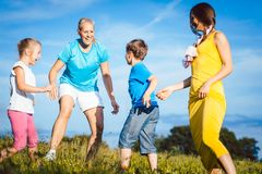 Two women with children playing tag stock image