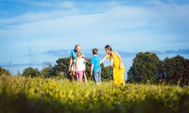 Two women with children playing tag royalty free stock images